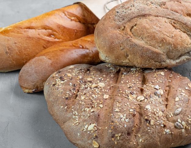 Свежий домашний хрустящий хлеб и багеты крупным планом на сером фоне
