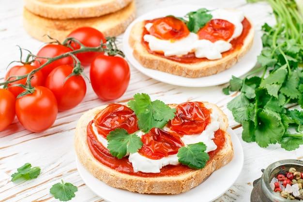 Fresh homemade crispy bruschetta with baked tomatoes cherry, cream cheese (ricotta), red sauce and parsley