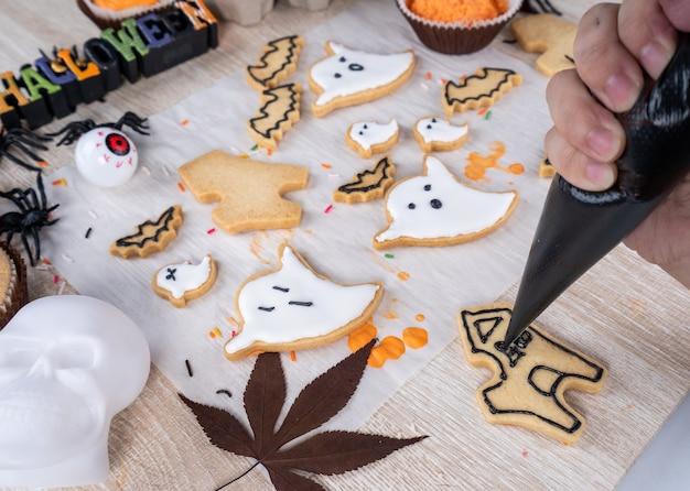 Свежий домашний украшающий десерт на хэллоуин с призраком, ползучим пауком, летучей мышью, замком с привидениями и ужасающим глазным яблоком на деревянном фоне, копией пространства