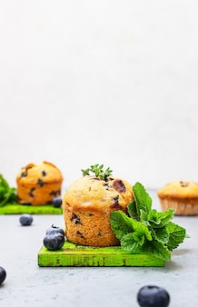 Fresh homemade delicious blueberry muffins decorated with thyme, berries and mint