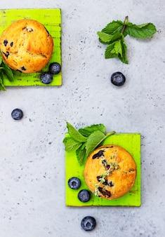 タイム、フレッシュベリー、ミントで飾られた新鮮な自家製のおいしいブルーベリーのマフィン。