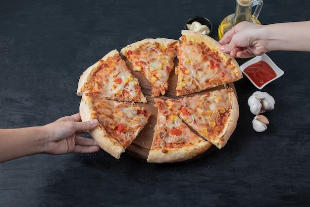 신선한 수제 맛있는 피자. 여성 손 복용 피자 조각입니다. 광각.