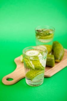 녹색 배경에 유리잔에 담긴 유기농 오이로 만든 신선한 홈메이드 디톡스 물