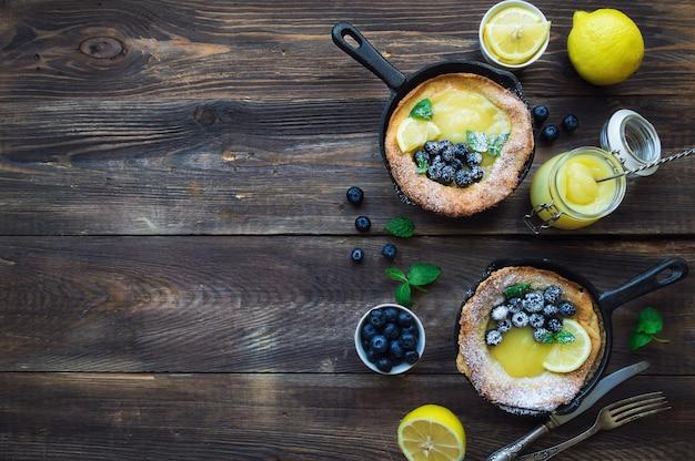素朴な木製の背景に鉄のフライパンでレモンカードとブルーベリーと新鮮な自家製ダッチベイビーパンケーキ。上面図。スペース領域をコピーします。