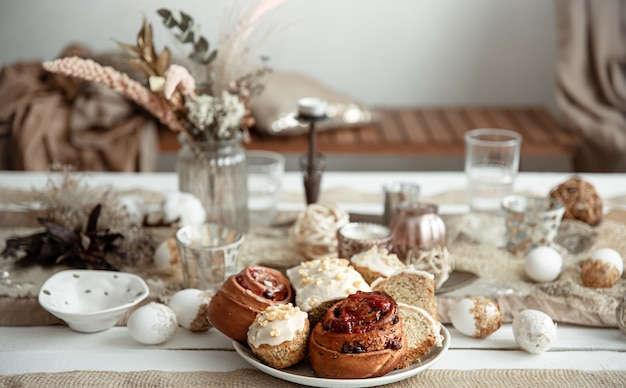 Fresh homemade easter baked goods on the holiday table with decor details on blurred background.