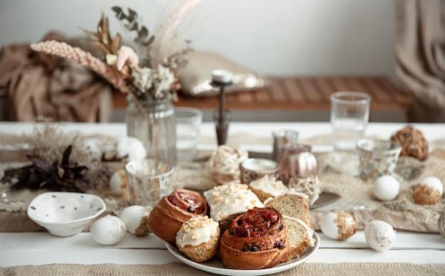 Свежая домашняя пасхальная выпечка на праздничном столе с деталями декора на размытом фоне.