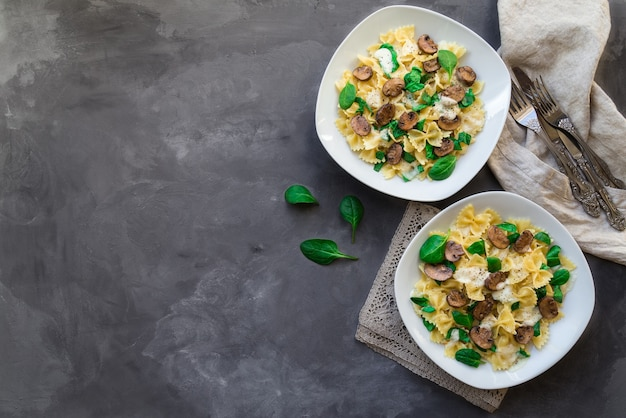 Fresh homemade farfalle pasta with mushrooms and spinach on concrete background
