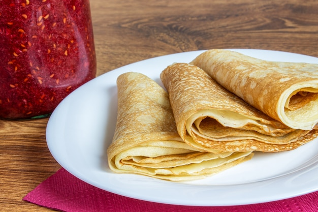 Fresh homemade folded crepe filled with strawberry jam on plate