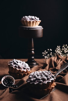 Свежий домашний фруктовый пирог на коричневой скатерти на черном фоне