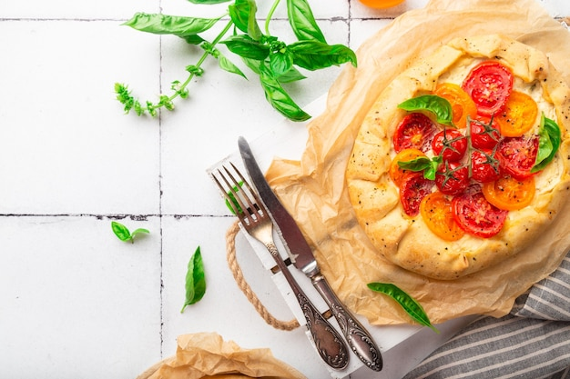 Fresh homemade galette with tomatoes ricotta cheese and basil on white tile background top view