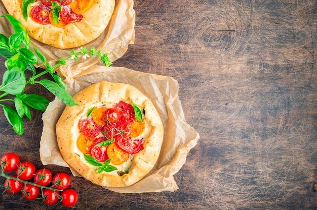 Свежие домашние галетты с помидорами, сыром рикотта и базиликом на деревенском фанерном фоне