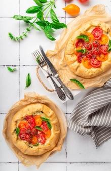 白いタイルの背景にトマト、リコッタチーズ、バジルの新鮮な自家製ガレット。上面図。