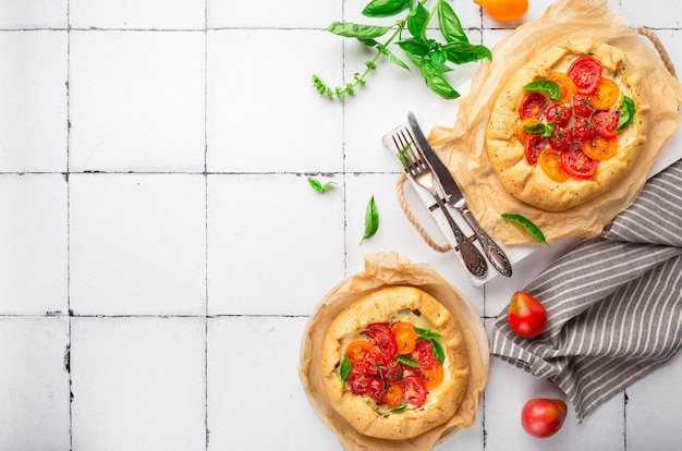 Fresh homemade galettes with tomatoes ricotta cheese and basil