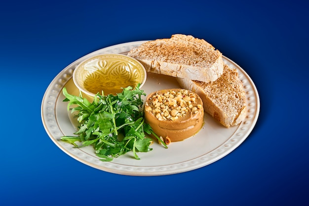 Fresh homemade goose liver pate with baguette, arugula, nuts and truffle honey on white plate. close up on tasty restaurant food.