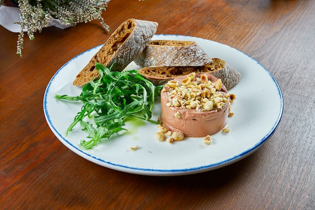 Fresh homemade goose liver pate with baguette, arugula, nuts and truffle honey on white plate on wooden table. close up on tasty restaurant food.