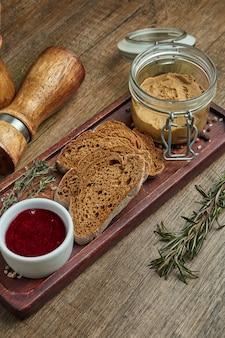 ライ麦パンとジャム木製トレイに新鮮な自家製のガチョウの肝臓のパテ。おいしいレストランの料理の平面図です。前菜