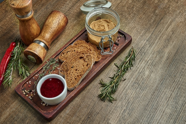 Fresh homemade goose liver pate with rye bread and jam on wooden tray. close up view with copy space