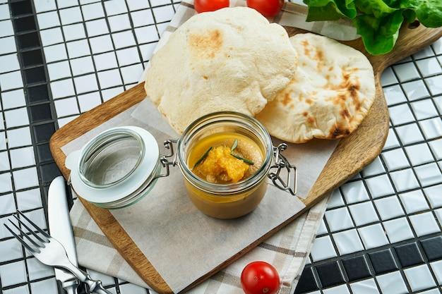 新鮮な自家製ガチョウまたは鶏レバーのパテ、フォカッチャ、クラフト紙。おいしいレストランの料理をクローズアップ。