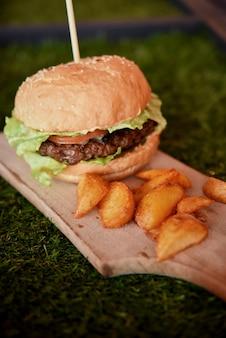 新鮮な自家製ハンバーガーと木の板に金色のジャガイモのスライス Premium写真