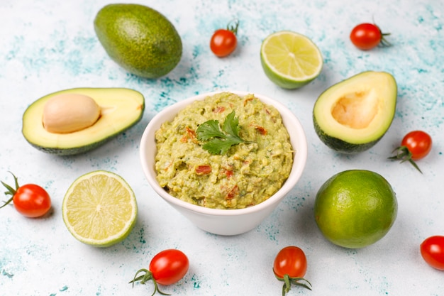 Fresh homemade hot guacamole sauce with ingredients, top view