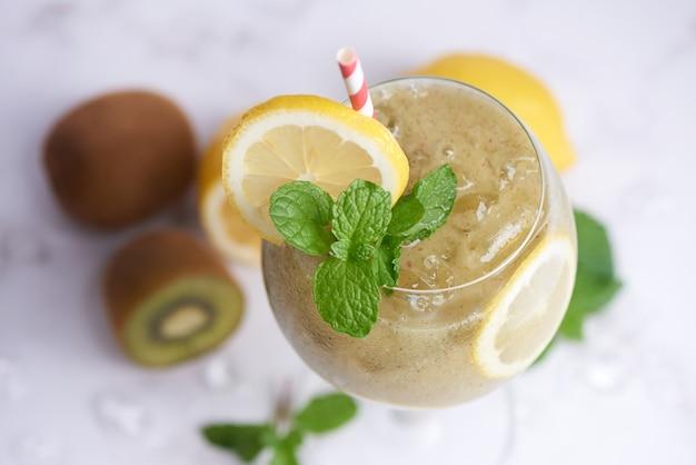 レモン、ミルク、ミント、ハチミツを使った新鮮な自家製キウイスムージー。ヘルシーなオーガニックドリンク。クローズ アップとセレクティブ フォーカス。ブレンドしたての緑の果物、健康、減量のコンセプト。