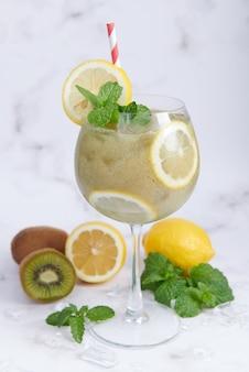Свежие домашние смузи из киви с лимоном, молоком, мятой и медом. здоровый органический напиток. крупным планом и выборочный фокус. свежеприготовленные зеленые фрукты, концепция благополучия и потери веса.