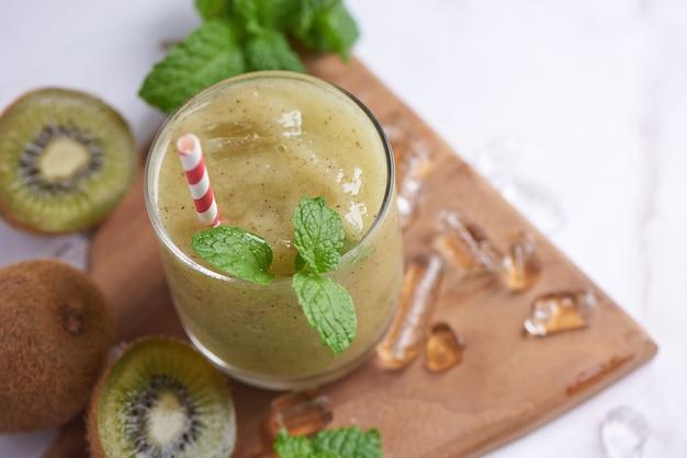 Свежие домашние смузи из киви с молоком, мятой и медом. здоровый органический напиток. крупным планом и выборочный фокус. свежеприготовленные зеленые фрукты, концепция благополучия и потери веса.