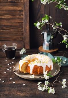 素朴な木製の背景に白い釉薬と皮で飾られた新鮮な自家製レモンバントケーキ
