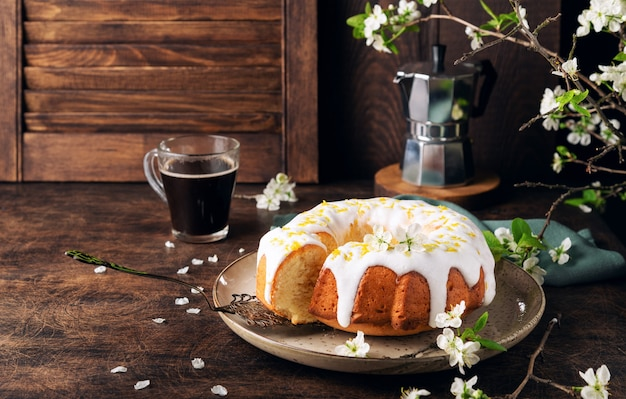 Fresh homemade lemon bundt cake decorated with white glaze and zest on rustic wooden background