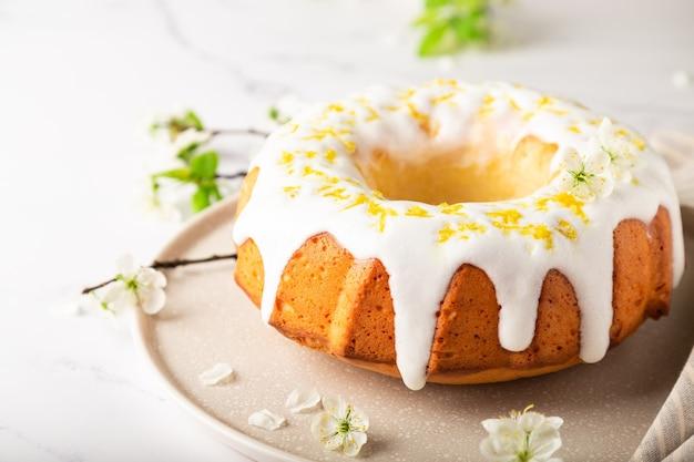 Fresh homemade lemon cake decorated with white glaze and zest on white marble background