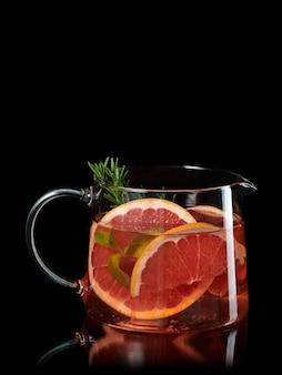 黒で分離されたガラスのカラフにグレープフルーツとローズマリーの新鮮な自家製レモネード