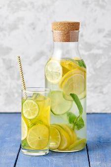 Свежий домашний лимонад с лаймом и мятой в стакане с бумажной трубочкой и бутылкой на ярко-синем фоне
