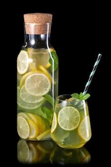 Свежий домашний лимонад с лаймом, мятой и льдом в бутылке и стакане с бумажной соломкой на черном фоне