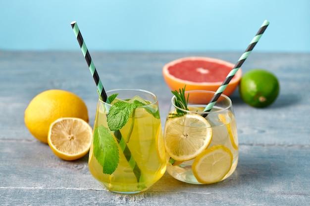 Свежий домашний лимонад с лаймом, мятой, розмарином, тимьяном и льдом в стакане с бумажной соломкой на синем фоне