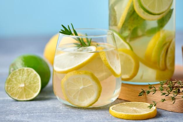 Свежий домашний лимонад с лаймом, розмарином, тимьяном и льдом в стакане с бумажной соломкой на синем фоне