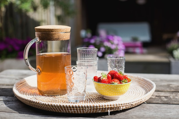 Fresh homemade lemonade with strawberries outdoors on the garden table in the summer colorful