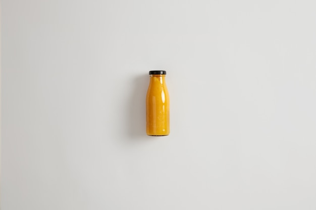 Fresh homemade mango pineapple orange smoothie in glass bottle isolated on white background. balanced combination of carbs, fiber, protein and healthy fats. beverage that maintains calorie deficit