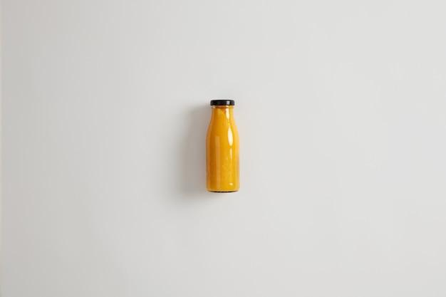 흰색 배경에 고립 된 유리 병에 신선한 홈 메이드 망고 파인애플 오렌지 스무디. 탄수화물, 섬유질, 단백질 및 건강한 지방의 균형 잡힌 조합. 칼로리 부족을 유지하는 음료