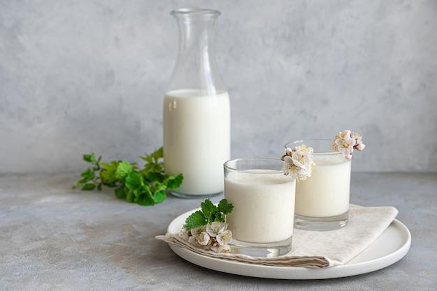 Свежий домашний молочный напиток, йогурт, кефир, айран, ласси в двух стаканах на серой стене с зеленью и цветами