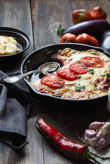 Fresh homemade moussaka in iron skillet on rustic wooden background with ingredients. greek cuisine.
