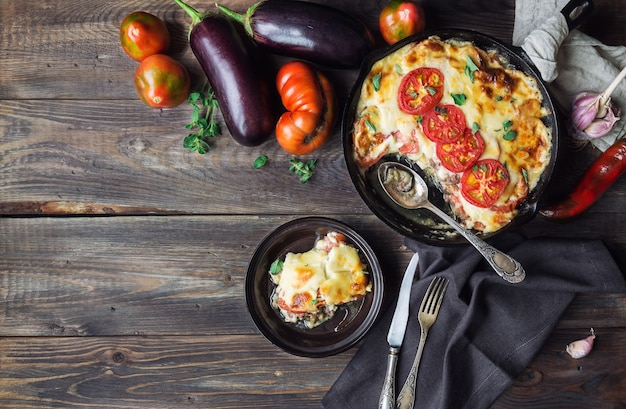 Fresh homemade moussaka in iron skillet on rustic wooden background with ingredients greek cuisine