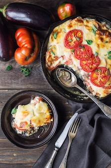 Fresh homemade moussaka in iron skillet on rustic wooden background with ingredients