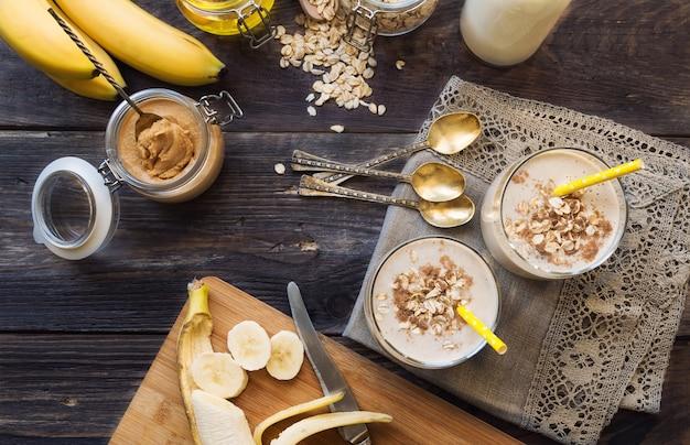 Свежий домашний питательный смузи с банановыми овсяными хлопьями и арахисовым маслом на деревянном фоне