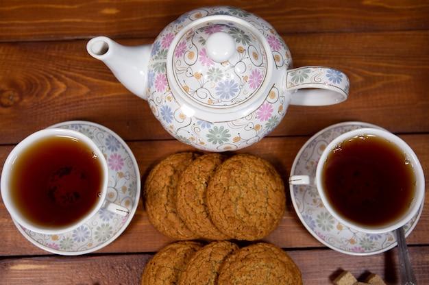 Свежее домашнее овсяное печенье с чайным сервизом на темном деревянном фоне