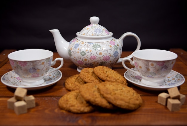 Fresh homemade oatmeal cookies with a tea set on a dark wooden background