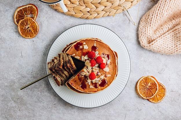 白いキテンの背景にアーモンド、ラズベリー、コーヒーと新鮮な自家製パンケーキ。居心地の良い朝食。上面図。フラットレイ