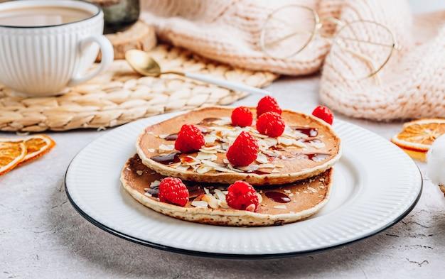 白いキテンの背景にアーモンド、ラズベリー、コーヒーと新鮮な自家製パンケーキ。居心地の良い朝食