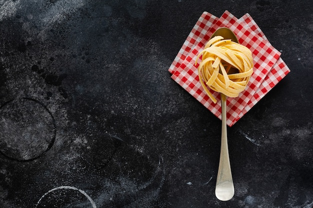 Fresh homemade pasta tagliatelle on wooden spoon with pasta ingredients tomatoes, raw egg, basil leaf on the dark concrete table table. cooking concept. top view with copy space.