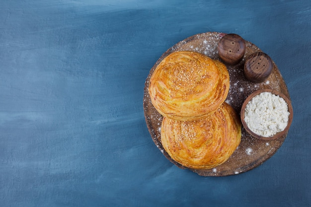 Fresh homemade pastries and bowl of flour on wood piece.