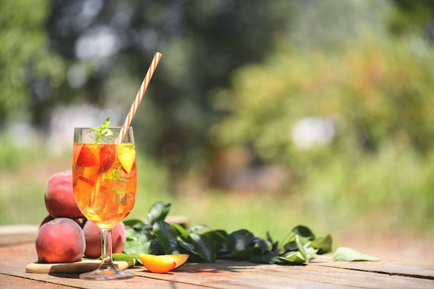 ミントとピーチスライスを使った新鮮な自家製ピーチスウィートティー、夏の冷たいフルーツドリンクを屋外で。木製のテーブルにカラフルなカクテルとモクテル